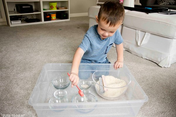 Toddler playing in a rice bin activity from Busy Toddler focusing on scooping and trasnfering rice.