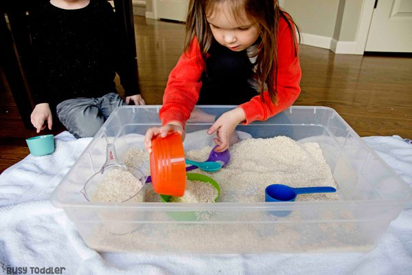 Toddler playing in a sensory bin filled with rice