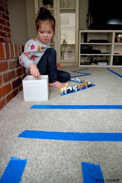 Preschooler playing with a simple kids activity: she's lining up animal figurines onto strips of blue painters tape in a simple toddler or preschool activity from Busy Toddler