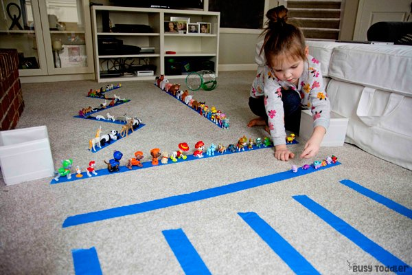 Preschooler playing with a simple kids activity: she's lining up animal figurines onto strips of blue painters tape as an Animal Line-up in a simple toddler or preschool activity from Busy Toddler