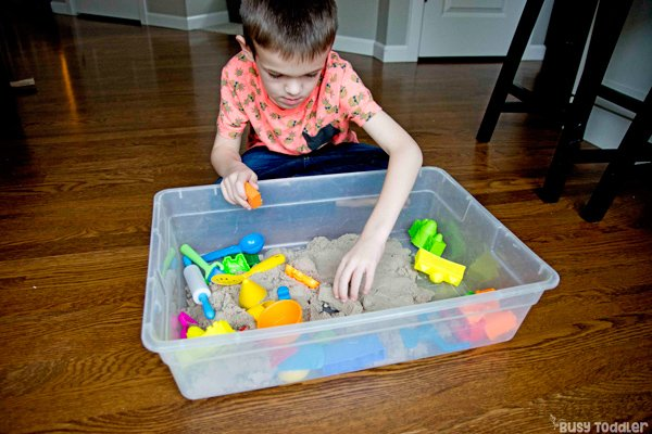 A kindergartener playing with a sensory bin in a big kid activity from Busy Toddler