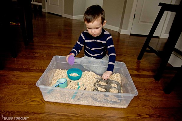 Toddler doing a taste-safe sensory bin filled with oatmeal