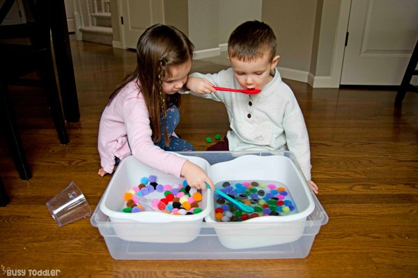 A toddler and preschooler playing in a pom pom ball sensory bin using water