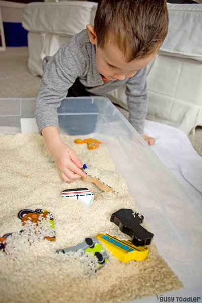 Toddler playing with a sensory bin and puzzles activity where he is looking for puzzle pieces that have been mixed up and sorted in a rice sensory bin (a great toddler activity from Busy Toddler)