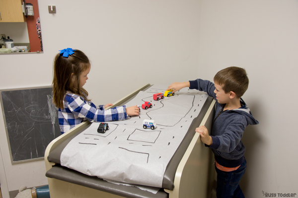 Two kids playing in a doctor's office with a homemade road on the check up table as they wait to be seen