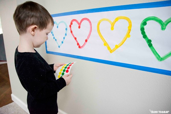 A toddler playing with a dot sticker sorting activity matching colors to hearts