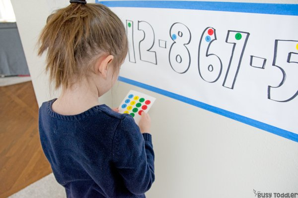 A preschool activity to help kids learn their phone number - photo showing a preschooler using dot stickers to sort the digits in her phone number from Busy Toddler