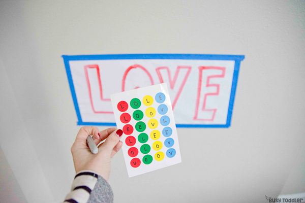 Preschooler working on a dot sticker activity for Valentine's Day