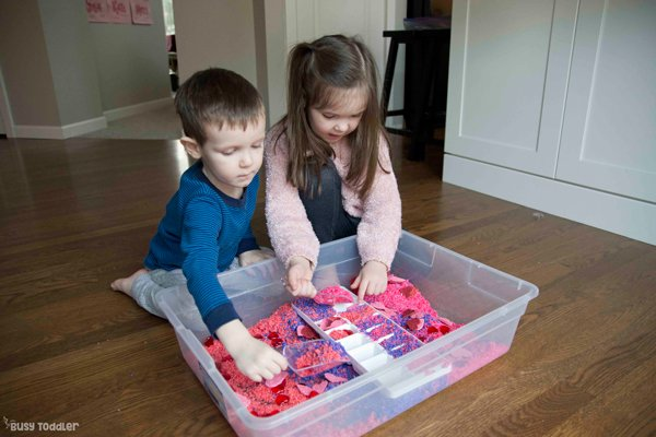 Toddler and Preschooler playing with a simple Valentine's Day themed sensory bin created by Busy Toddler