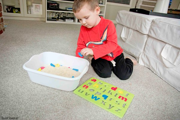 A toddler playing with a dollar store ABC puzzle with pieces hidden in rice