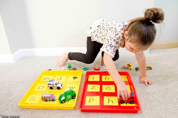 A preschooler working on a phonemic awareness activity from Busy Toddler