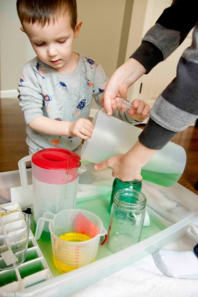 Siblings playing with an indoor water activity learning to pour while they stay at home
