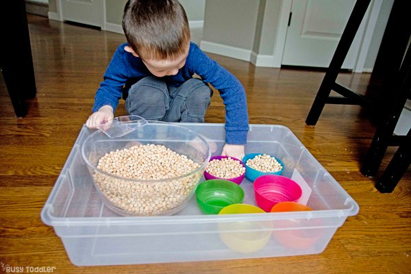 A toddler playing with a simple Montessori activity scooping beans from a large bowl to six smaller bowls.