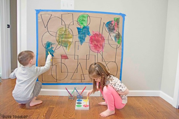 Shape and art activity from Busy Toddler with two kids painting overlapping shapes on Kraft paper