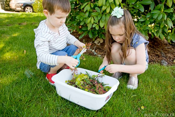 Two kids learning about cutting skills using yard clippings to practice with