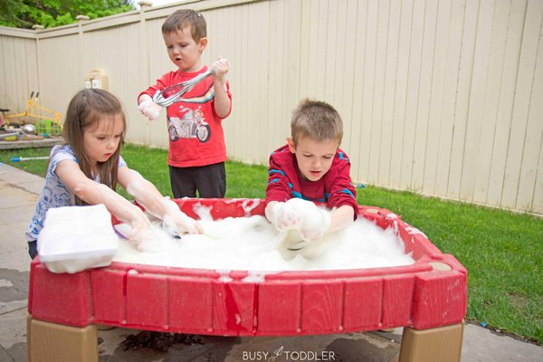 Siblings playing in a water table filled with Bubble Foam in a quick activity from Busy Toddler