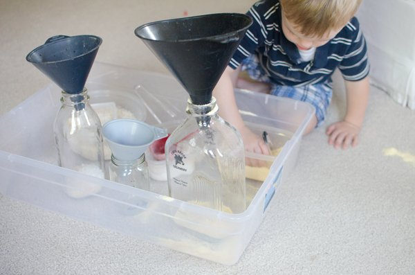 A toddler playing with a fun sensory scooping activity from Busy Toddler