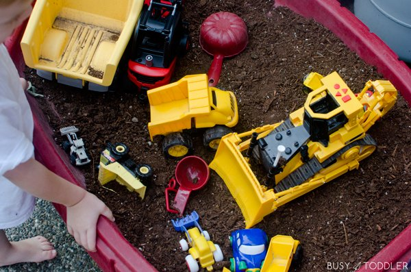 A fun toddler activity playing in a dirt filled sand box.