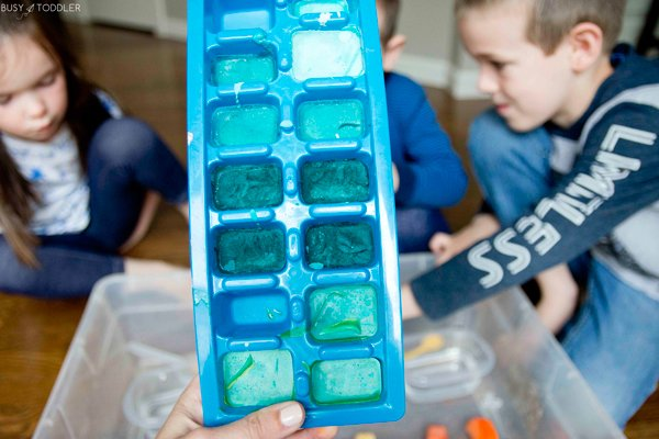 Kids playing with a frozen baking soda activity from Busy Toddler