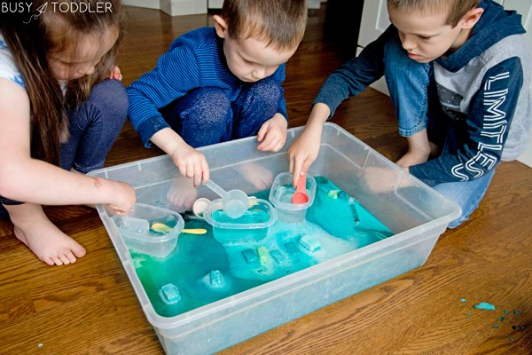 Kids playing at a science experiment activity from Busy Toddler