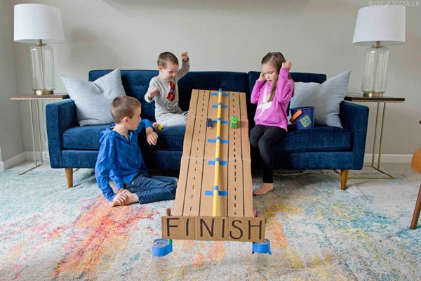 Kids watching a car race down a cardboard ramp in a quick and easy activity.