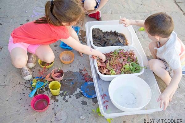 Kids playing with a fun sensory activity: a mud kitchen!
