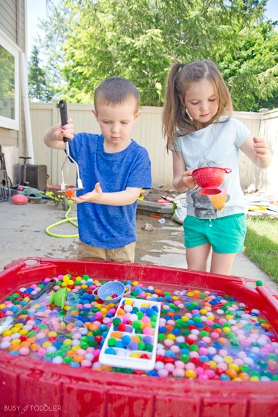Kids playing with wet pom pom balls in a sensory bin