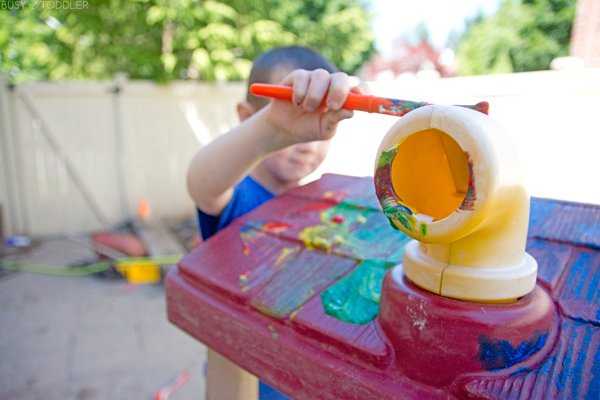 Kids playing an outdoor painting activity from Busy Toddler