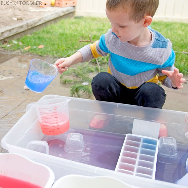 Toddler playing with water that's been dyed with tempera paint