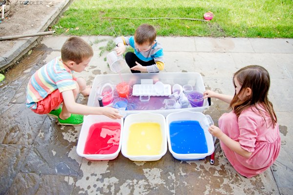 Siblings playing with water that's been dyed with tempera paint