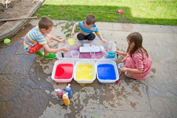 Kids playing with water dyed with tempera paint in a fun kids activity