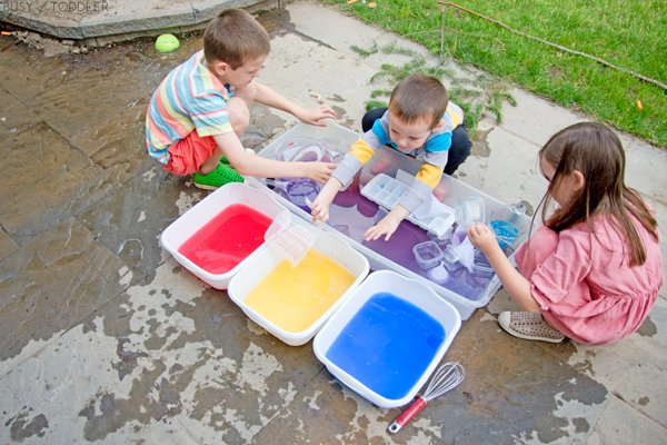 Siblings playing with water dyed with tempera paint in a fun kids activity