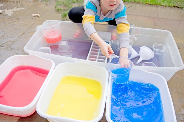 Toddler playing with water dyed with tempera paint in a fun kids activity
