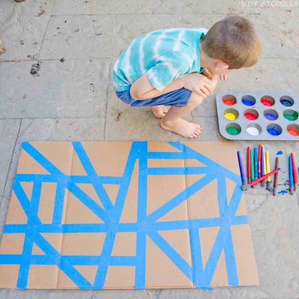 A child doing a tape resist art kids activity.