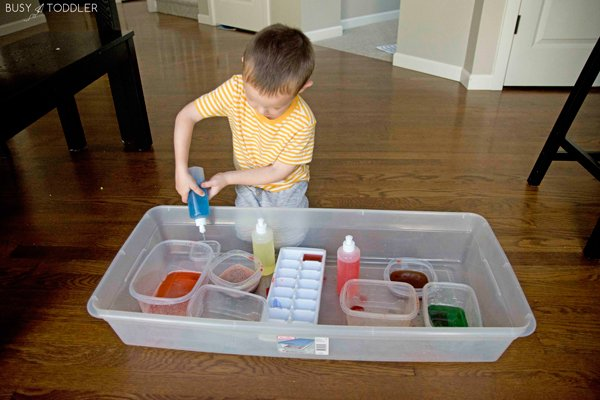 Kid playing at a colored water mixing station using peri bottles to hold the liquid from Busy Toddler