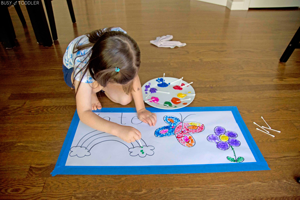 A girl using Q-tips to make a pointillism type art activity from Busy Toddler