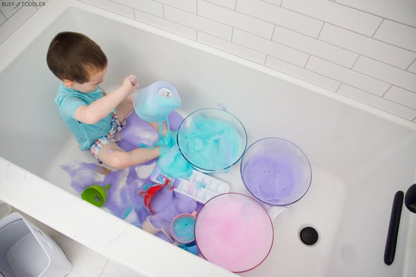 A toddler playing with bubble foam in a bath time activity.