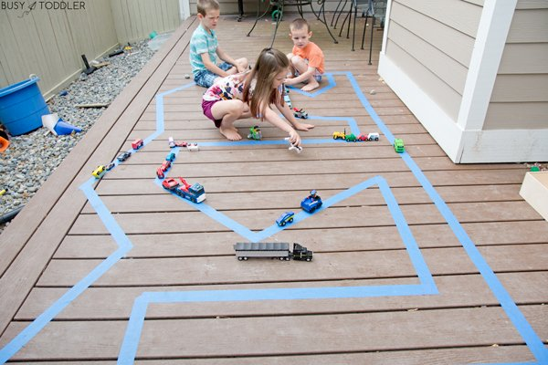 Kids playing with a road made out of tape on a deck outside