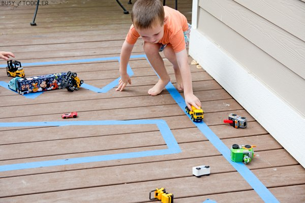 A toddler playing with a road made out of tape on a deck outside