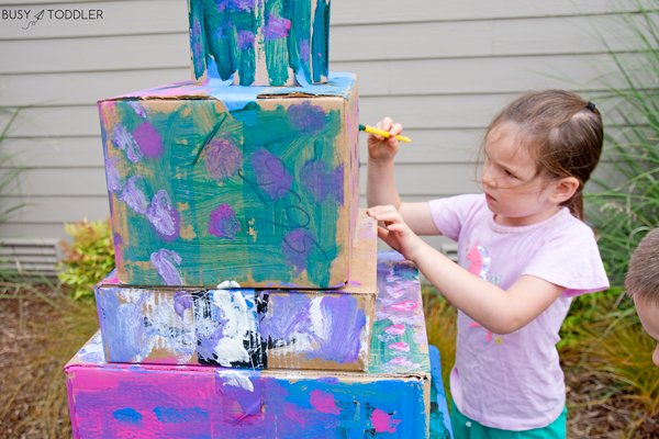 A child making a painted tiered box cake as a fun outdoor activity