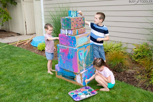 Kids making a painted tiered box cake as a fun outdoor activity