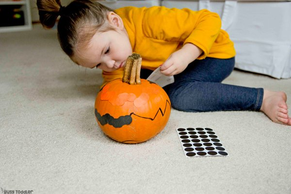 A toddler playing with a fun Halloween activity using dot stickers