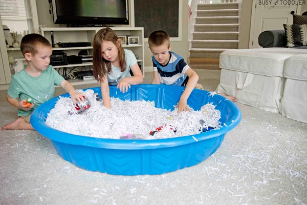 A toddler playing in a sensory bin filled with shredded paper