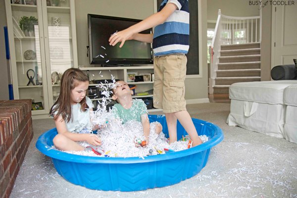 Siblings playing in a sensory bin filled with shredded paper