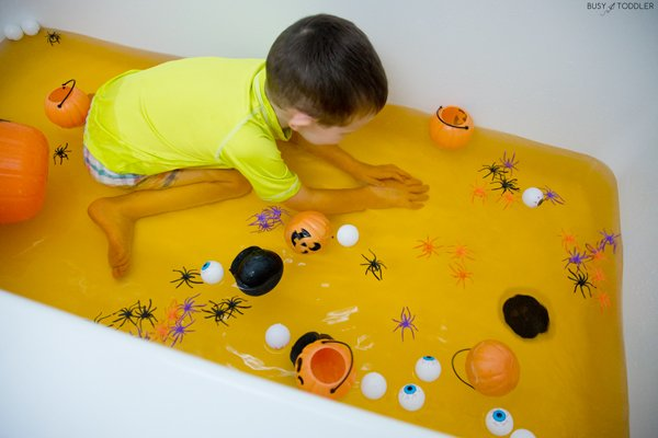 Toddler playing in a Halloween bath activity
