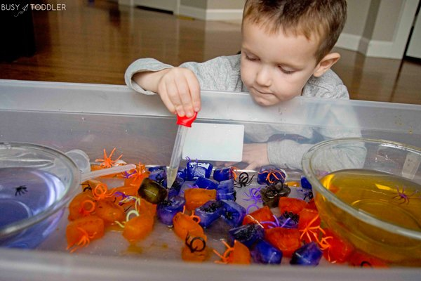 Child playing with ice cubes and plastic spiders in a Halloween science activity