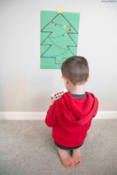 Preschooler plays a Christmas math activity using dot stickers - Busy Toddler