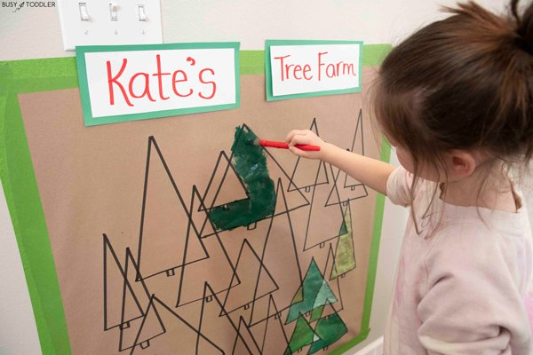 A child painting a Christmas art project over overlapping triangle trees like a tree farm