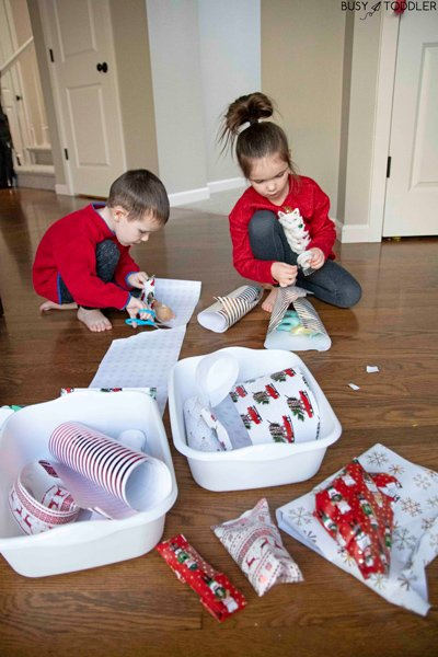 Siblings gather together at a holiday wrapping station to make homemade gifts for each other
