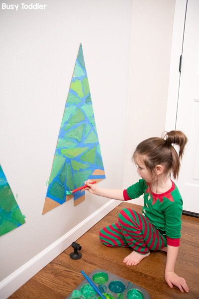 Kids painting Christmas trees in a tape resist art activity
